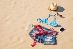 Attrezzatura dell'abbigliamento di estate delle ragazze in sabbia Immagini Stock