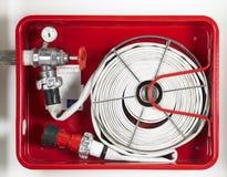Attrezzatura della manichetta antincendio in una scatola metallica rossa Immagini Stock