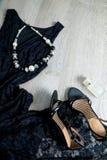 Attrezzatura delle donne Vestito dal pizzo, sandali della scarpa, collana e profumo neri su fondo di legno grigio Vista superiore Immagini Stock