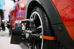 Attrezzatura di allineamento della ruota su una ruota di automobile Fotografia Stock