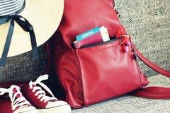 Attrezzatura di estate delle donne: scarpe da tennis rosse, zaino, cappello, cuffie Materie di viaggio del turista e del fondo Fotografia Stock
