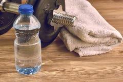 Attrezzatura di forma fisica di concetto con la testa di legno, bottiglia di acqua ed asciugamano Immagini Stock