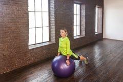 Attrezzatura di ginnastica Donna che fa posa del gatto nella palla di forma fisica Fotografie Stock Libere da Diritti