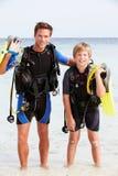 Attrezzatura di immersione con bombole di And Son With del padre sulla festa della spiaggia Fotografie Stock Libere da Diritti