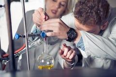 Attrezzatura di laboratorio per distillazione Mani dello studente/interno/tecnico che mostrano esperimento Lavorando nei gruppi p Fotografia Stock