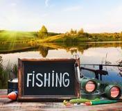 Attrezzatura di pesca e una lavagna Fotografia Stock