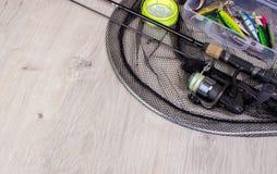 Attrezzatura di pesca - filatura, ganci e richiami di pesca su fondo di legno immagine stock