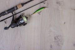 Attrezzatura di pesca - filatura, ganci e richiami di pesca su fondo di legno leggero fotografia stock