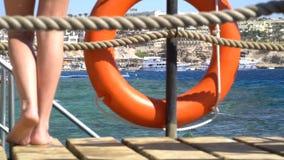 Attrezzatura di sicurezza, salvagente o boa di salvataggio sul pilastro di legno alla spiaggia 120fps stock footage