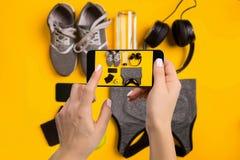 Attrezzatura di sport che fotografa sul telefono cellulare Lo schermo di Smartphone con forma fisica foggia l'immagine fotografia stock libera da diritti