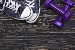 Attrezzatura di sport e di forma fisica: scarpe da tennis, teste di legno su fondo di legno Fotografia Stock
