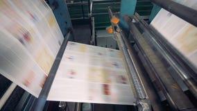 Attrezzatura di tipografia nel lavoro, fine su I fogli di carta fastly vanno su un trasportatore ad una fabbrica stock footage