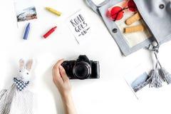 Attrezzatura di turismo dei bambini con i giocattoli e macchina fotografica sulla disposizione bianca del piano del fondo Fotografie Stock