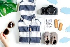 Attrezzatura di turismo dei bambini con i vestiti e macchina fotografica sulla disposizione bianca del piano del fondo Fotografie Stock Libere da Diritti