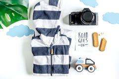 Attrezzatura di turismo dei bambini con i vestiti e macchina fotografica sulla disposizione bianca del piano del fondo Immagini Stock Libere da Diritti