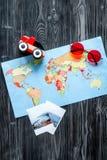 Attrezzatura di turismo dei bambini con la mappa ed immagini sulla disposizione scura del piano del fondo Fotografia Stock Libera da Diritti