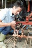 Attrezzatura di Working On Agricultural dell'agricoltore in granaio Immagine Stock Libera da Diritti