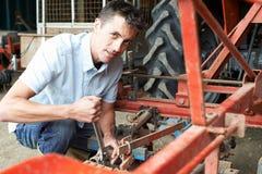 Attrezzatura di Working On Agricultural dell'agricoltore in granaio Fotografia Stock Libera da Diritti