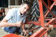 Attrezzatura di Working On Agricultural dell'agricoltore in granaio Immagine Stock