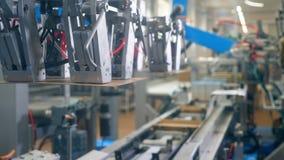 Attrezzatura moderna della fabbrica Il meccanismo robot sta riassegnando i contenitori di cartone e sta imballandoli video d archivio