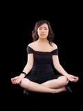 Attrezzatura nera meditating di posa della giovane donna asiatica Immagini Stock