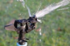 Attrezzatura per irrigazione a pioggia di acqua in giardino Fotografia Stock Libera da Diritti