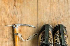 Attrezzatura rampicante: scarpe di trekking, strumenti del ghiaccio, ascia di ghiaccio, ramponi su fondo di legno, vista superior Fotografia Stock