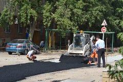 Attrezzatura speciale sulla riparazione della strada. Stenditura dell'asfalto. Fotografie Stock