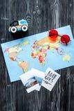 Attrezzatura turistica con la mappa per il viaggio con la vista superiore del fondo di legno scuro dei bambini Fotografie Stock Libere da Diritti