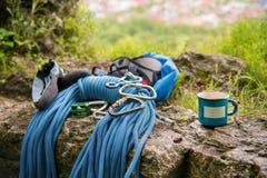 Attrezzatura utilizzata per la scalata dove i carabiners della corda e la scalata delle pantofole accanto alla tazza su cui un pi Fotografia Stock Libera da Diritti