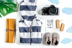 Attrezzatura, vestiti e macchina fotografica turistici per il viaggio con la vista superiore del fondo bianco dei bambini Immagine Stock