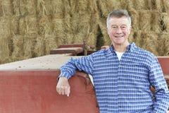 Attrezzature agricole di Standing Next To dell'agricoltore in granaio Immagini Stock