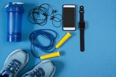 Attrezzature e scarpe di sport con il telefono cellulare su fondo blu fotografia stock