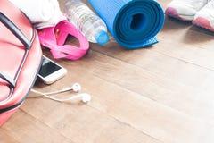 Attrezzature ed accessori con il telefono cellulare per l'allenamento della donna Fotografia Stock