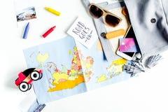 Attrezzature turistiche con la mappa e giocattoli per il viaggio con i bambini sulla vista superiore del fondo bianco Fotografie Stock