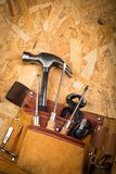 Attrezzi per bricolage in cinghia dello strumento sul piatto di legno urgente immagini stock libere da diritti