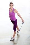 Attrezzo ginnico femminile con le gomme Immagini Stock