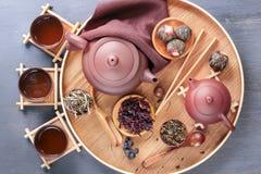 Attribut för den kinesiska teceremonin, flera typer av grönt te, keramisk tekanna på ett trämagasin cups liten tea arkivbild