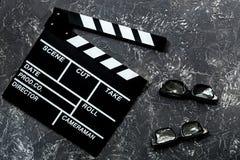 Attribute des Filmregisseurs Filmclapperboard und -Sonnenbrille auf Draufsicht des grauen Steintabellenhintergrundes Lizenzfreies Stockfoto