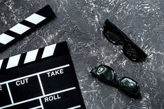 Attributes of film director. Movie clapperboard and sunglasses on grey stone table background top view Royalty Free Stock Photo