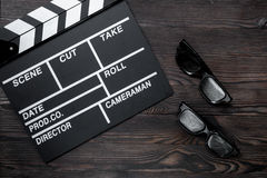 Attributes of film director. Movie clapperboard and sunglasses on wooden table background top view Stock Photos