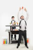 Attributes of good barman. Full length portrait of two handsome bartenders one of which holding bar spoon with some cocktail on the top Stock Image