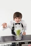 Attributes of good barman. Half-length portrait of dark-haired bartender standing at the bar counter and preparing some green cocktail Stock Image