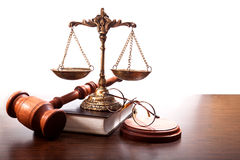 The attributes of a judge. Glasses, book,gavel, bronze scales with small plates on the chains on the table Royalty Free Stock Photography