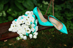 Attributes runaway bride. Wedding bouquet of white roses and blue ribbons and blue patent leather high-heeled shoes Stock Photography
