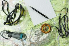 Attributes of a tourist. Determining the direction of movement during a trip on a tourist map using a compass. royalty free stock photography