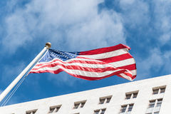 Attributes of the US culture. American state flag against the background of the City Hall in Los Angeles. Los Angeles, California, USA - March 21, 2017: high stock photo