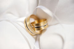 Attributes of the wedding, wedding rings of yellow metal on a white pillow. Stock Photos