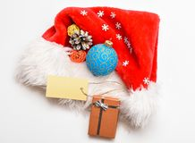 Attributes of winter holidays. New year and christmas celebration. Santa hat with christmas gift box. Keep family stock image