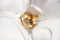 Attributi delle nozze, fedi nuziali di metallo giallo su un cuscino bianco Fotografie Stock